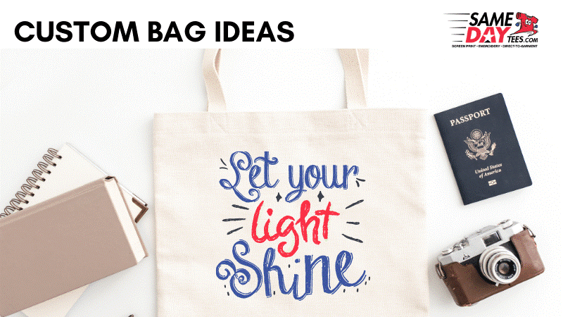 """White Tote bag with the text - """"Let your light shine"""" - surrounded by a passport, camera and some note pads. Custom Bad Ideas written above the image"""